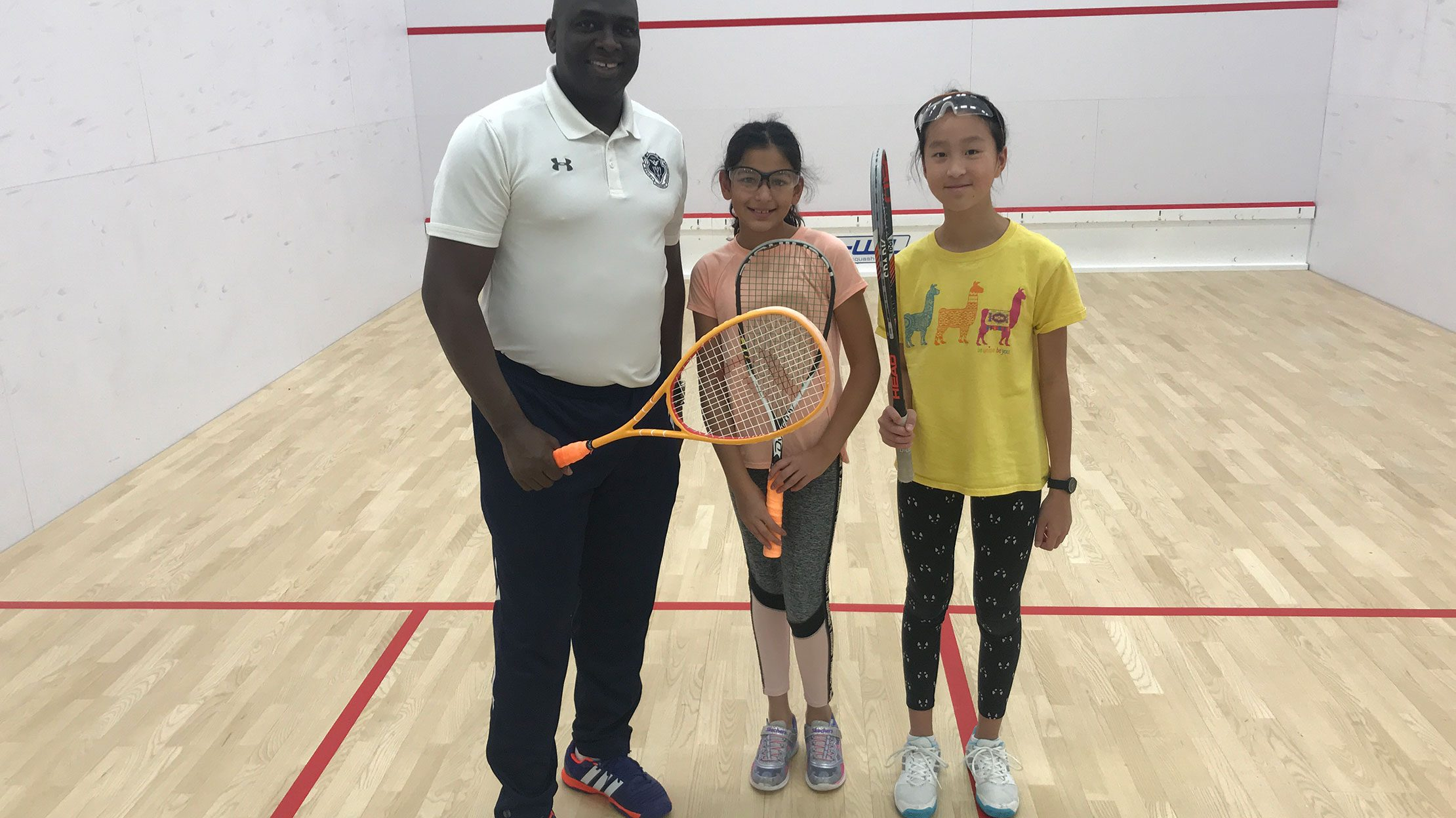 An instructor standing with two girls on a squash court.