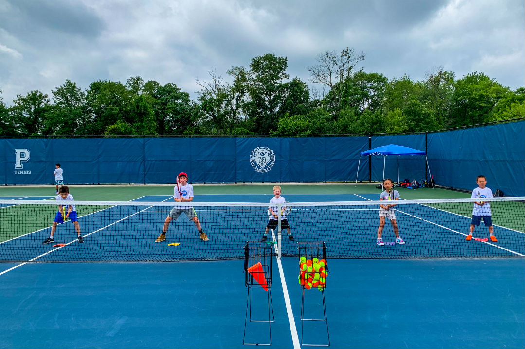 Five kids getting ready to practice for tennis